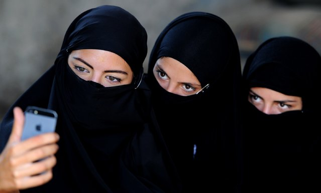 "Georgian actors take a picture of themselves wearing veils before taking part in a joint Georgian-US military counterterrorism exercise called ""Agile Spirit 2014"" at the Vaziani military base outside Tbilisi on June 18, 2014. (Photo by Vano Shlamov/AFP Photo)"