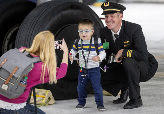 A boy gets his picture taken during the sixth annual Santa's Winter Wonderland event, held by Delta Air Lines, at the Salt Lake City International Airport on Saturday, December 7, 2019. After taxiing on a decorated Boeing 737 to the Delta hangar, patients from Primary Children's Hospital and Shriners Hospitals for Children-Salt Lake City, and their families, enjoyed games, presents and fun. (Photo by Scott G. Winterton/Deseret News)