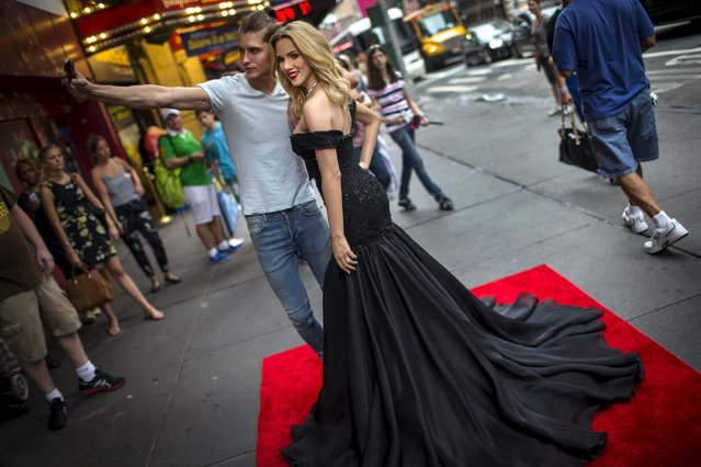 A model takes a selfie with a wax figure of U.S. actress Scarlett Johansson as it stands outside Madame Tussauds New York attraction shortly after the figure was unveiled in Times Square in New York, July 30, 2015. (Photo by Mike Segar/Reuters)