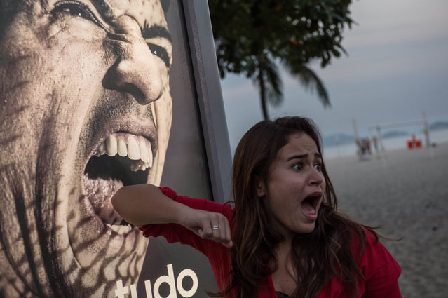 A tourist jokes in front of an advertisement with the portrait of Uruguay's forward Luis Suarez at Copacabana beach in Rio de Janeiro, Brazil, on June 26, 2014. (Photo by Yasuyoshi Chiba/AFP Photo)