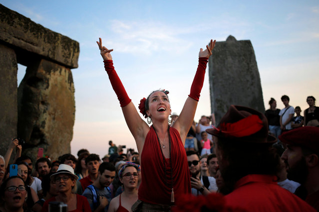 A singer leads hundreds of fellow revelers in song while waiting for the sun to set during the summer solstice festival at Stonehenge, Salisbury, Britain, 20 June 2017 (Issued 21 June 2017). The annual festival attracts hundreds of people to the 5000 year old stone circle to mark the longest day in the northern hemisphere. sunrise was at 4.52am and was celebrated by dancing, music, and ritualistic events around the stones. (Photo by Kim Ludbrook/EPA)