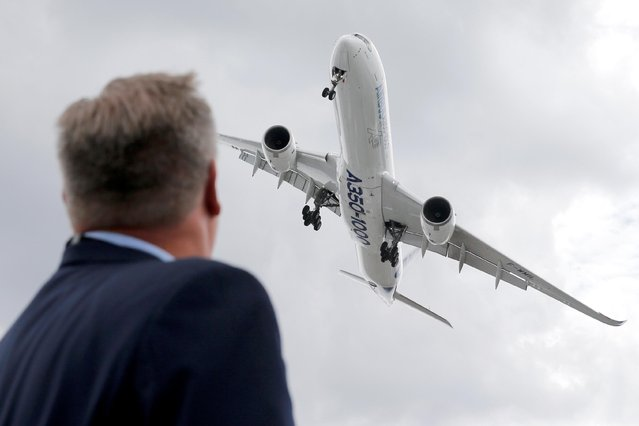 A visitor looks at an Airbus A350-1000 as he performs during the 53rd International Paris Air Show at Le Bourget Airport near Paris, France on June 19, 2019. (Photo by Pascal Rossignol/Reuters)