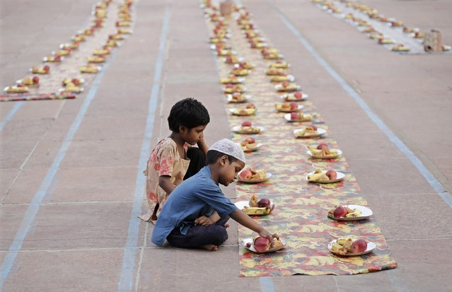 Children sit next to food placed for Muslims before the Iftar (breaking of fast) meal, during the holy fasting month of Ramadan in India, at the Jama Masjid (Grand Mosque) in the old quarters of Delhi July 1, 2014. (Photo by Anindito Mukherjee/Reuters)