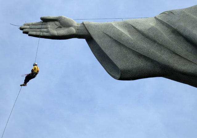 """A worker rappels from the Cristo Redentor statue at the Corcovado in Rio de Janeiro June 23, 2014. In a project called """"On The Sidelines"""" Reuters photographers share pictures showing their own quirky and creative view of the 2014 World Cup in Brazil. (Photo by Alessandro Garofalo/Reuters)"""