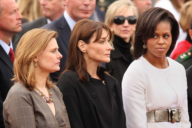 First Lady Michelle Obama (R) stands with Carla Bruni-Sarkozy and Sarah Brown during a memorial service at the Normandy American Cemetery on June 6, 2009 in Colleville-sur-Mer, France. (Photo by Peter Macdiarmid/Getty Images)