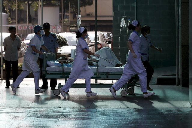 Medical personnel transport a victim of a factory explosion, at a hospital in Kunshan, Jiangsu province, in this August 2, 2014 file picture. China has ramped up its healthcare reform rhetoric, touting greater access for foreign investors to healthcare services, a bigger role for technology and pushing drug sales from mostly state-run hospitals towards the retail market. (Photo by Aly Song/Reuters)