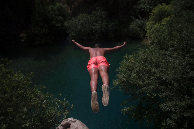 """A boy jumps into the Guadiaro river at """"La Cueva del Gato"""" (The Cove of the Cat) near Benaojan, in southern Spain on July 13, 2017. (Photo by Jorge Guerrero/AFP Photo)"""