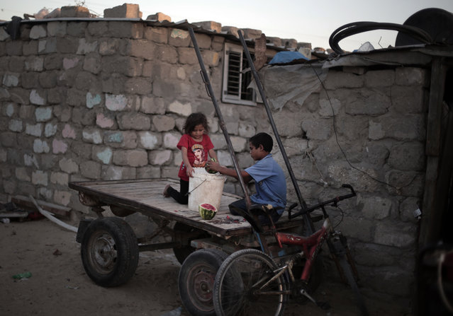 In this Monday, June 20, 2016 photo, Palestinian children prepare food for a horse as they sit on a cart next to their house in El-Zohor slum on the outskirts of Khan Younis refugee camp, southern Gaza Strip. The expansion of the el-Zohor slum, where barefoot children play in the rusty skeletons of discarded vehicles surrounded by mountains of garbage, is a sign of the times in Gaza, where poverty is growing and there is little hope for the future. While Gaza has always been poor, conditions for the 1.8 million people who live in the crowded seaside territory worsened since the Islamic militant group Hamas seized power in 2007. (Photo by Khalil Hamra/AP Photo)