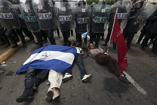 Opposition supporters lie down on the ground in front of a line of riot police officers during a protest in front of the Supreme Electoral Council (CSE) building in Managua, Nicaragua August 12, 2015. (Photo by Oswaldo Rivas/Reuters)
