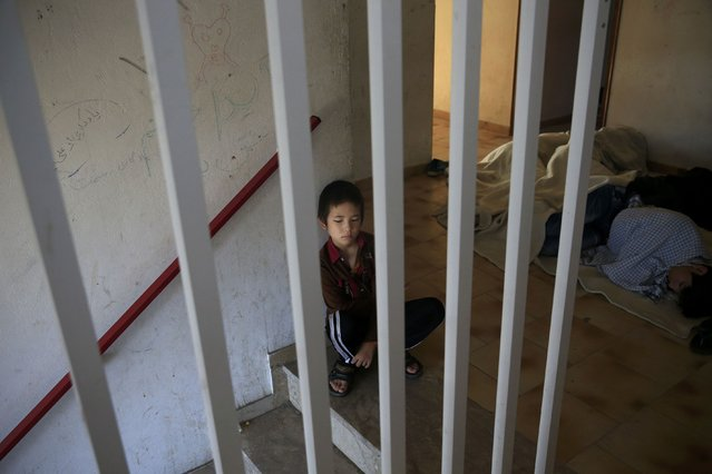 A migrant boy from Afghanistan sits at the staircases of a deserted hotel on the Greek island of Kos, August 13, 2015. (Photo by Alkis Konstantinidis/Reuters)