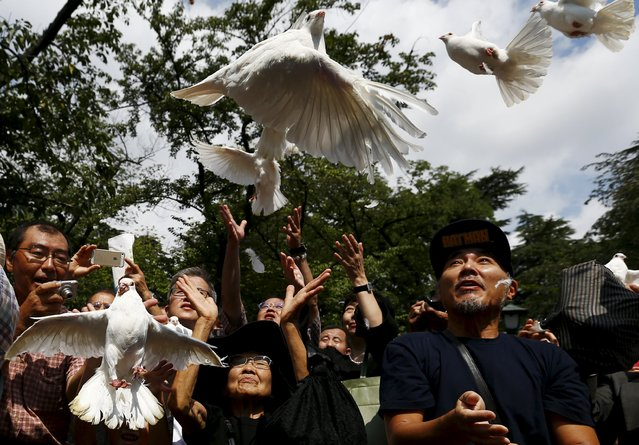 People release doves as a symbol of peace at Yasukuni Shrine on the anniversary of Japan's surrender in World War Two in Tokyo August 15, 2015. (Photo by Thomas Peter/Reuters)