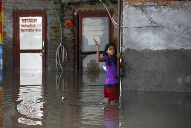 A girl holds onto a pole as as she stands in floodwaters flowing from the swollen Bagmati River caused by heavy rainfall in Kathmandu, Nepal August 17, 2015. (Photo by Navesh Chitrakar/Reuters)
