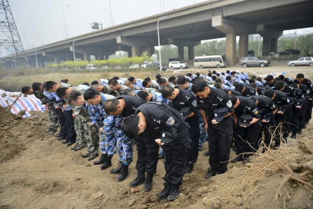 Representatives from the police and People's Liberation Army (PLA), marking the seventh day since the Tianjin explosions, pay tribute to the people who died, in a ceremony at Binhai new district, Tianjin, China, August 18, 2015. Hundreds of residents displaced by huge explosions last week in the Chinese port of Tianjin demanded compensation on Monday, as authorities worked to complete a sweep of the blast site for dangerous chemicals. (Photo by Reuters/Stringer)