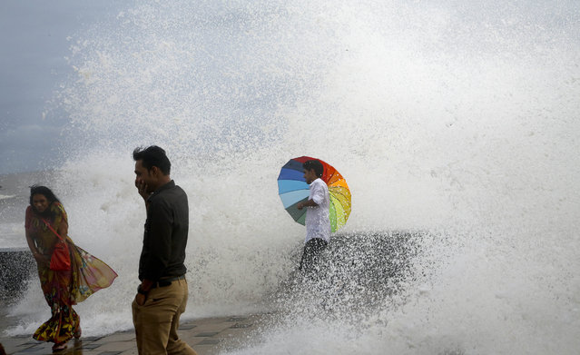 An Indian man holding an umbrella stands on the Arabia Sea coast as he enjoys the high tide waves in Mumbai, India, Wednesday, June 29, 2016. Monsoon rains have picked up pace in the city after a slow start, bringing welcome relief after a long drought. The monsoon season runs from June to September and the next few weeks are forecast to be normal or wetter-than-normal in much of India. (Photo by Rajanish Kakade/AP Photo)