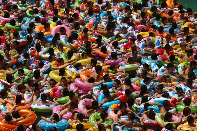 This picture taken on July 25, 2014 shows people cooling off in a waterpark in Suining, southwest China's Sichuan province. Meteorological departments issued an orange alert for high temperature as a heat wave embraces Sichuan province, with temperature of most area topped 37, local media reported. (Photo by AFP Photo)