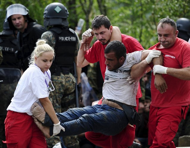 Red Cross workers assist a collapsed migrant after he crossed Greece's border with Macedonia, in Gevgelija, Macedonia, August 22, 2015. (Photo by Ognen Teofilovski/Reuters)