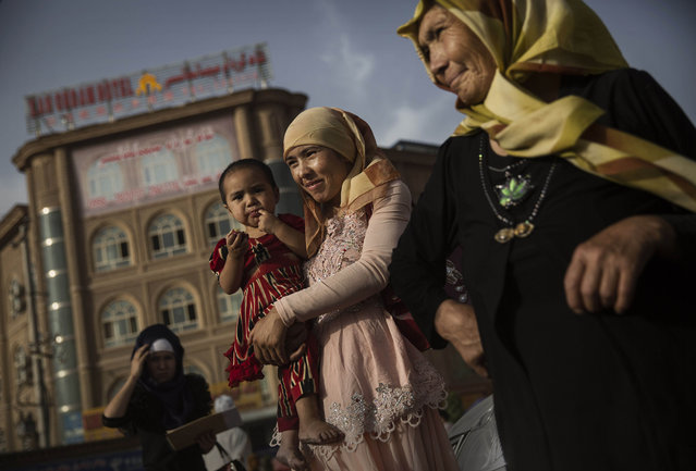 A Uyghur woman walks with her baby at a market on August 1, 2014 in old Kashgar, Xinjiang Province, China. (Photo by Kevin Frayer/Getty Images)