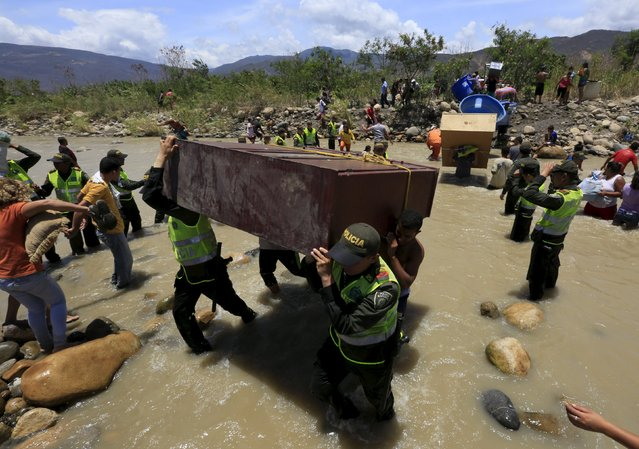 Colombian policemen carry items belonging to people arriving in Colombia while crossing the Tachira river border with Venezuela, near Villa del Rosario village August 25, 2015. (Photo by Jose Miguel Gomez/Reuters)