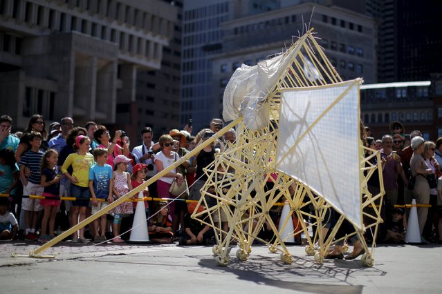 "Onlookers watch a display of ""Animaris Ordis"", one from the series of ""Strandbeests"" kinetic sculptures by Dutch artist Theo Jansen, at City Hall Plaza in Boston, Massachusetts August 28, 2015. A pair of skeletal sculptures that harness the power of the wind to walk strutted around Boston's City Hall on Friday at the start of the U.S. tour of Jansen's ""Strandbeests."" (Photo by Brian Snyder/Reuters)"