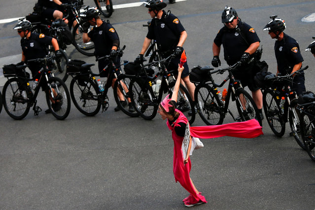 """An activist with Code Pink poses next to police on bicycles monitoring a protest march by various groups, including """"Black Lives Matter"""" and """"Shut Down Trump and the RNC"""" ahead of the Republican National Convention in Cleveland, Ohio, U.S., July 17, 2016. (Photo by Adrees Latif/Reuters)"""