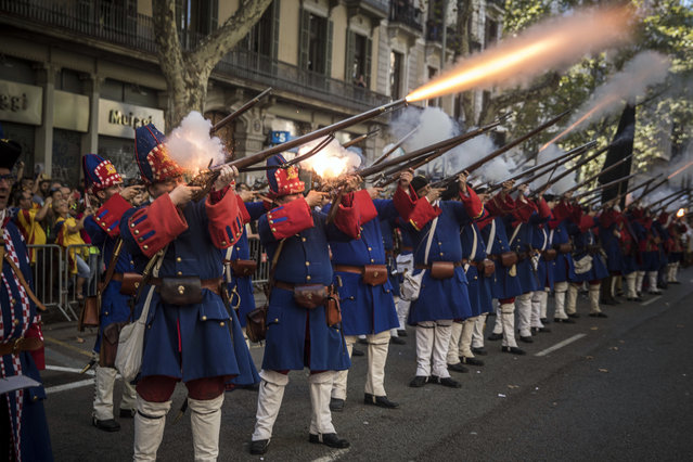 Men wearing reproductions of Catalan military costumes of the 18th century shoot blaze weapons during a performance during the Catalan National Day in Barcelona, Spain, on Monday, September 11, 2017. Hundred of thousands of people are expected to demonstrate in Barcelona to call for the creation of a new Mediterranean nation, as they celebrate the Catalan National Day holiday. (Photo by Santi Palacios/AP Photo)