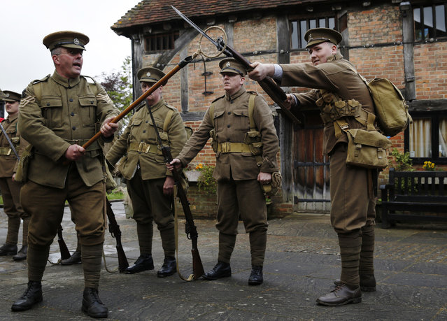 Factory landlord Lawrence Taylor (L), portraying a Colour Sergeant from the King's Royal Rifle Corps, part of the Rifles Living History Society, performs a drill with Connor Young (R) of the Queen's Own Royal West Kent Regiment Living History Group as they recreate the life of a First World War soldier at the Eden Valley Museum in Edenbridge in southeast England May 10, 2014. (Photo by Luke MacGregor/Reuters)
