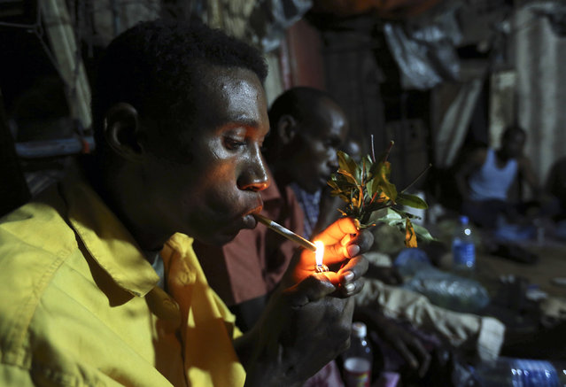 Somali men smoke and chew khat inside a makeshift building at night in Mogadishu August 6, 2014. (Photo by Thomas Mukoya/Reuters)