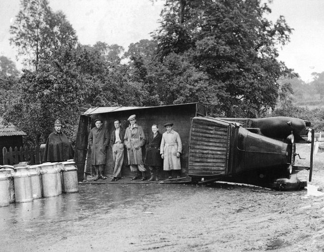 Passers-by use an overturned lorry as a shelter during a sudden shower of rain near Navestock, Romford, Essex. The lorry overturned on a sharp bend, discharging its load of milk churns, but the driver escaped uninjured. 15th June 1937. (Photo by Fox Photos)