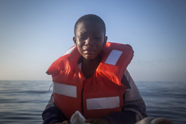 In this Thursday, July 28, 2016 photo, Dustin, 11, from Nigeria, who said his mother died in Libya, cries aboard a Spanish NGO's boat, after being rescued from an overcrowded rubber boat during a rescue operation on the Mediterranean Sea, about 23 kilometers (14 miles) north of Sabratha, Libya. (Photo by Santi Palacios/AP Photo)