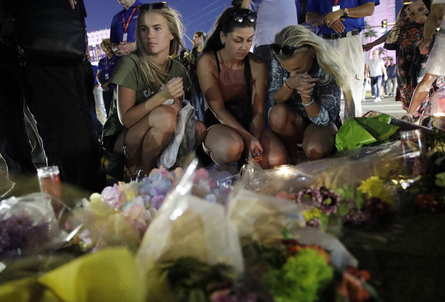 People pause at a memorial set up for victims of a mass shooting in Las Vegas, Nev., on Tuesday, October 3, 2017. A gunman opened fire on an outdoor music concert on Sunday. It was the deadliest mass shooting in modern U.S. history, with dozens of people killed and hundreds injured, some by gunfire, some during the chaotic escape. (Photo by John Locher/AP Photo)