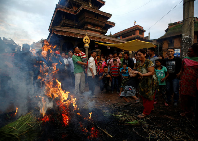 A woman (R) swings a child near a fire, where an effigy of the demon Ghantakarna was burnt to symbolize the destruction of evil, during the Ghantakarna festival at the ancient city of Bhaktapur, Nepal August 1, 2016. (Photo by Navesh Chitrakar/Reuters)