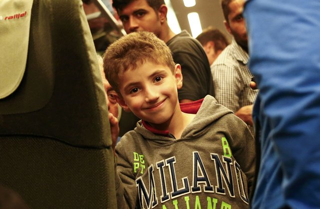A migrant boy smiles aboard a train to Vienna departed from the railway station in the town of Hegyeshalom, Hungary, September 5, 2015. (Photo by Leonhard Foeger/Reuters)