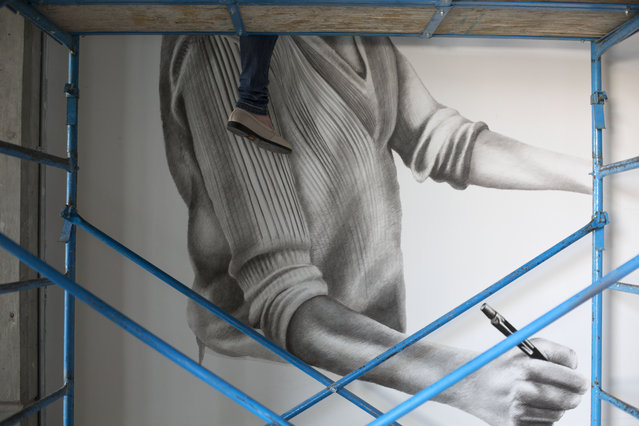 """In this September 1, 2015 photo, artist Beatriz Avila Haro's foot hangs from scaffolding as she paints a mural for Street Art Chilango inside the offices of an architecture firm, in the Condesa neighborhood of Mexico City. Ricardo del Razo, the architect who commissioned that project, said the 12-foot-tall mural will show a woman pressing a pencil to the drawing board, """"devising how to solve problems"""". (Photo by Rebecca Blackwell/AP Photo)"""