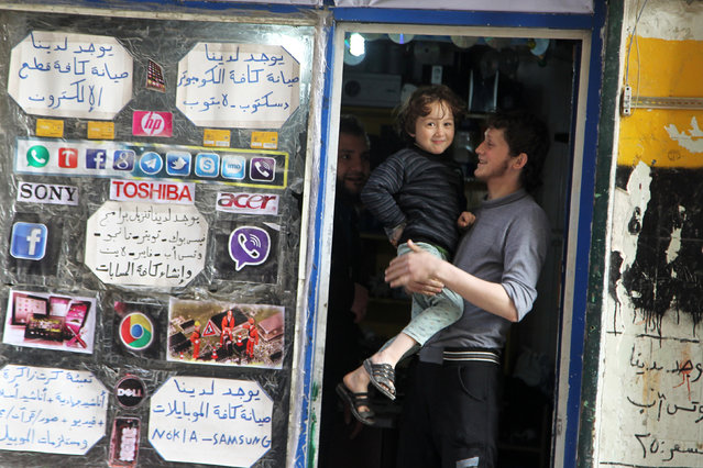 Gymnast Ahmad al-Sawas carries his brother Hadi as he stands at the door of his father's shop in the rebel-held Bustan al-Qasr neighbourhood of Aleppo, Syria March 23, 2016. (Photo by Abdalrhman Ismail/Reuters)