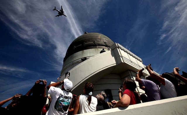 Shuttle fans watch as Endeavour flies over Griffith Park Observatory in Los Angeles. (Photo by Brian van der Brug/Los Angeles Times/MCT)