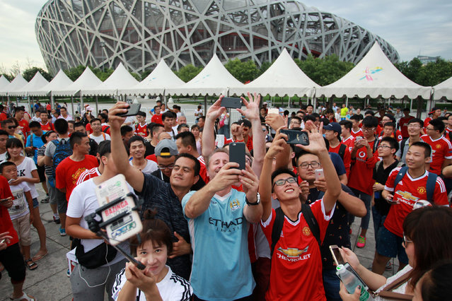 Fans take selfies as they gather near the National Stadium, also known as the Bird's Nest stadium, after the match between Manchester United and Manchester City was called off in Beijing, China, July 25, 2016. (Photo by Reuters/Stringer)