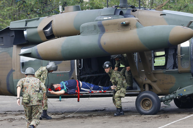 A man rescued by a Ground Self-Defense Force helicopter on a stretcher arrives at an evacuation center in Joso, Ibaraki prefecture, northeast of Tokyo, Friday, September 11, 2015. (Photo by Shizuo Kambayashi/AP Photo)