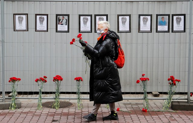 A woman wearing a protective mask holds flowers near a makeshift memorial for medics, who reportedly died in Saint Petersburg and Leningrad Region in the times of the coronavirus disease (COVID-19) outbreak, in central Saint Petersburg, Russia on April 28, 2020. (Photo by Anton Vaganov/Reuters)