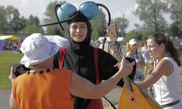"""In this frame grab provided by the APTN a woman dressed as a mosquito enjoys with others a sunny Sunday, August 14, 2016, during the Russia Mosquito Festival in the town of Berezniki. 9-year-old Irina Ilyukhina won the """"tastiest girl"""" category with 43 bites to show for going berry-picking in the forest with her mother. (Photo by AP Photo)"""