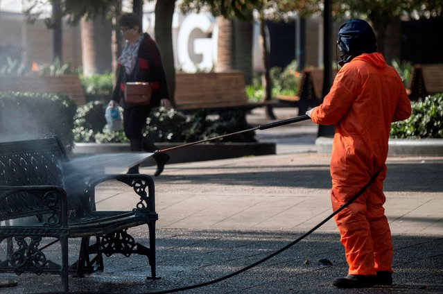 A Municipality worker cleans and disinfects the Mayor square in Santiago, on June 10, 2020 amid the new coronavirus pandemic. (Photo by Martin Bernetti/AFP Photo)
