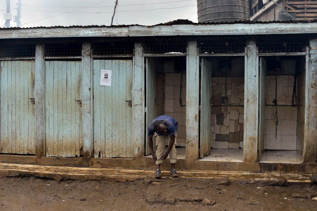 A man rolls up his trousers before using a public toilet on November 8, 2017 in the Kibera slum of Nairobi, Kenya. (Photo by Simon Maina/AFP Photo)