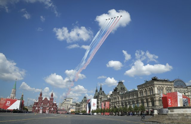 Russian warplanes fly over Red Square leaving trails of smoke in colors of national flag during the Victory Day military parade marking the 75th anniversary of the Nazi defeat in Moscow, Russia, Wednesday, June 24, 2020. The Victory Day parade normally is held on May 9, the nation's most important secular holiday, but this year it was postponed due to the coronavirus pandemic. (Photo by Alexander Zemlianichenko/AP Photo)