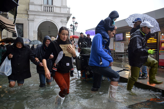 People walk in a flooded street during a 'acqua alta' on November 11, 2012 in Venice. Rain and wind hit the north of Italy on Sunday and the folooding reached 150 centimetres in Venice. (Photo by Marco Sabadin/AFP Photo)