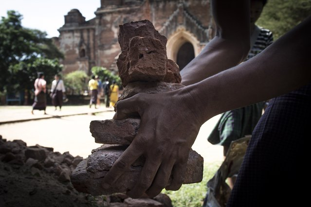 A man collects the pieces of bricks of Dhammayangyi temple after earthquake in ancient Bagan city, Myanmar on August 25, 2016. The magnitude 6.8 earthquake that rocked central Myanmar has left at least four people dead and more than 200 ancient temples and pagodas damaged, government officials said Thursday. (Photo by Kyaw Kyaw/Anadolu Agency/Getty Images)