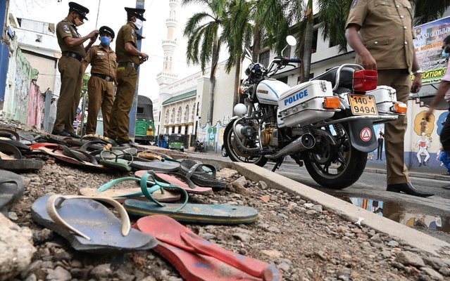 Policemen stand guard next to footwear scattered outside a warehouse, where three women were crushed to death in a stampede while waiting to receive a cash donation, in Colombo May 21, 2020. Three women who lined up to receive an eight dollar cash donation in Sri Lanka's curfew-bound capital were crushed to death in a stampede on May 21, police and residents said. About 1,000 men and women had formed separate queues outside a warehouse of a businessman to receive his annual cash donations during the holy month of Ramadan, local MP Mujibur Rahman said. (Photo by Lakruwan Wanniarachchi/AFP Photo)