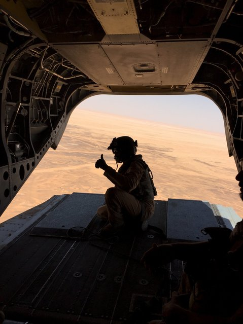 An Airman from the Emirati armed forces gives a thumbs up to a colleague during a flight from a base in Saudi Arabia to the frontline Yemeni province of Mareb September 14, 2015. (Photo by Noah Browning/Reuters)