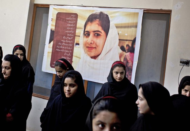In this Thursday, November 15, 2012 file photo, Pakistani girls gather under a poster of Malala Yousufzai in her old school in Mingora, Swat Valley, Pakistan. (Photo by Anja Niedringhaus/AP Photo)