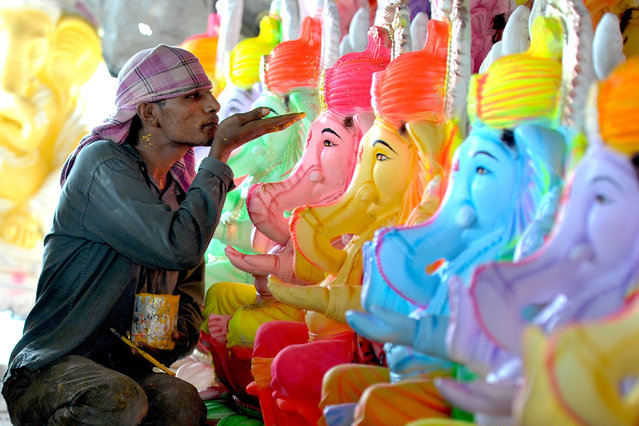 An Indian artists uses sparkles to decorate statues of the Hindu god Lord Ganesh ahead of the forthcoming Ganesh Chaturthi festival at a workshop in Hyderabad on August 29, 2016. The statues are being prepared for the Ganesh Chaturthi festival a popular eleven-day long Hindu religious festival in India which will be celebrated from September 5 to 15. (Photo by Noah Seelam/AFP Photo)