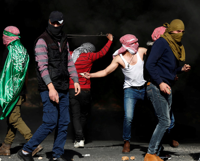 Palestinian protesters throw stones at Israeli forces during a protest against U.S. President Donald Trump's decision to recognize Jerusalem as the capital of Israel, near the Jewish settlement of Beit El, near the West Bank city of Ramallah December 11, 2017. (Photo by Goran Tomasevic/Reuters)