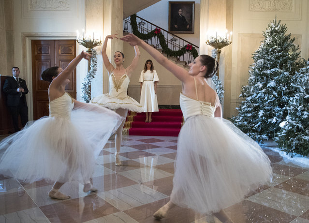 First lady Melania Trump watches as ballerinas perform a piece from The Nutcracker among the 2017 holiday decorations in the Grand Foyer of the White House in Washington, Monday, November 27, 2017. The First Lady honored 200 years of holiday traditions at the White House. (Photo by Carolyn Kaster/AP Photo)